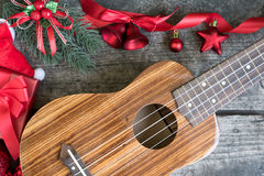 Ukulele on the wooden table with red christmas ornament. Ukulele on the wooden table with fir twigs and red christmas ornament decoration with gift box and santa Royalty Free Stock Photos