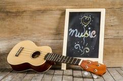 Ukulelegitarre und -tafel mit der Wort Musik geschrieben auf hölzernen Hintergrund Lizenzfreies Stockbild