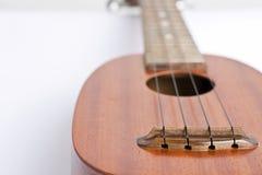 Ukulelemusikinstrument på den vita bakgrunden Fotografering för Bildbyråer