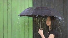 Ulewny deszcz nalewa na dziewczynie osłaniającej pod parasolem zbiory