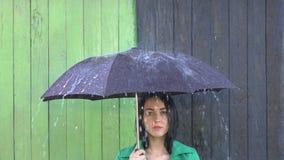 Ulewny deszcz nalewa na dziewczynie osłaniającej pod parasolem zbiory wideo