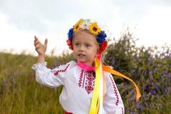 Little ukrainian girl in circlet of flowers. Ukrainian little girl and yellow field stock photography