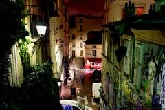 Ulica dziejowi budynki i sztuka współczesna graffiti na Montmartre nocą Październik 12th, Obrazy Stock
