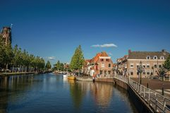 Ulica i most nad kanałem, cumować łodziami i cegła domami przy zmierzchem w Weesp, zdjęcie stock