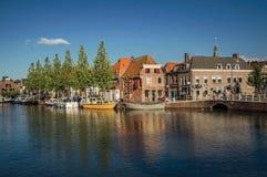 Ulica i most nad kanałem, cumować łodziami i cegła domami przy zmierzchem w Weesp, zdjęcia royalty free