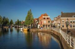 Ulica i most nad kanałem, cumować łodziami i cegła domami przy zmierzchem w Weesp, zdjęcie royalty free
