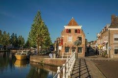 Ulica i most nad kanałem, cumować łodziami i cegła domami przy zmierzchem w Weesp, obraz royalty free