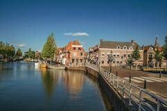 Ulica i most nad kanałem, cumować łodziami i cegła domami przy zmierzchem w Weesp, fotografia royalty free