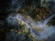 Ulica od above synkliny mglisty las przy jesienią, widok z lotu ptaka lataniem przez chmur z mgłą i drzewami, Obrazy Royalty Free