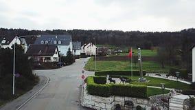 Ulica w małej wiosce w Szwajcaria Szwajcarska flaga rozwija w wiatrze zbiory