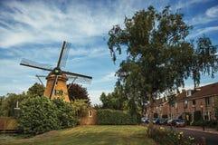 Ulica z drewnianym wiatraczkiem, obfitolistnymi krzakami, zielonym gazonem i domami pod pogodnym niebieskim niebem przy Weesp, Fotografia Stock