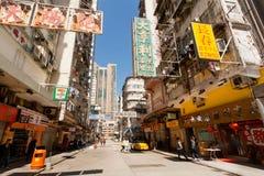 Ulica z dużo robi zakupy, nieociosani billboardy, wysocy scyscrapers i ludzie chodzi wokoło, obrazy royalty free