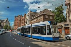 Ulica z niebieskim niebem, starymi budynkami i tramwajowym omijaniem obok w Amsterdam, Obraz Stock