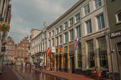 Ulica z pubami, tęczy flaga i ludźmi spaceruje na chmurnym dniu w s-Hertogenbosch, Fotografia Stock