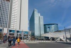Ulica z skrzyżowaniem ludzi za drapaczami chmur i innymi nowożytnymi budynkami miastowy miasto szklanymi i stalowymi Obrazy Stock