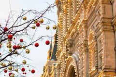 Ulicy w pełni dekorowali dla bożych narodzeń z czerwonymi i złocistymi piłkami Choinka w mieście Dom iluminujący z światłami dużo zdjęcia royalty free