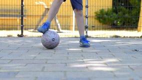 Uliczna piłki nożnej chłopiec drybluje z piłką zbiory