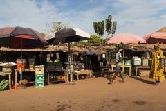 Uliczna scena w mieście Bissau z kobietą jest ubranym kolorową suknię i chłopiec w ulicznym rynku w Bissau, Zdjęcie Stock