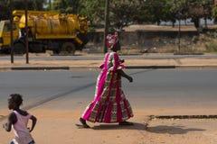 Uliczna scena w mieście Bissau z kobietą jest ubranym kolorowego smokingowego odprowadzenie w ulicie w Bissau, Obraz Royalty Free