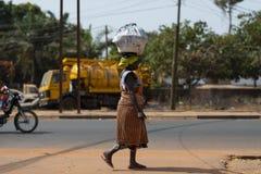 Uliczna scena w mieście Bissau z kobietą jest ubranym kolorowego smokingowego odprowadzenie w ulicie i przewożeniu taca na jej gł Zdjęcia Royalty Free