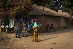 Uliczna scena w mieście Bissau z kobietami jest ubranym kolorowego sukni buyng odziewa w ulicznym rynku w Bissau, Zdjęcie Stock