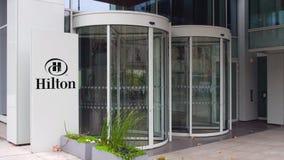 Uliczna signage deska z Hilton Hotels Ucieka się loga zbudować nowoczesnego urzędu Redakcyjny 3D rendering Obrazy Royalty Free