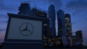 Uliczna signage deska z Mercedes-Benz logem w wieczór Zamazany dzielnica biznesu drapaczy chmur tło editorial Obraz Stock