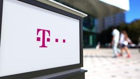 Uliczna signage deska z T-Mobile logem Zamazani biura odprowadzenia i centrum tła ludzie Redakcyjny 3D rendering Zdjęcia Stock