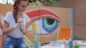 Uliczna sztuka, nastolatek z aerosolową farbą przy tłem graffiti w zwolnionym tempie, uliczny obraz, dziewczyna z kiścią zbiory wideo