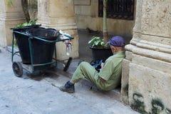 Ulicznego wymiatacza siedzący puszek w ganeczku obok jego fury naprawia torbę obrazy stock