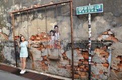Uliczni malowidła ściennego tittle dzieci na huśtawce malowali Louis Gan mnie Zdjęcia Stock