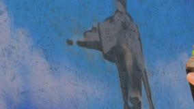 Uliczny artysta maluje kolorowych graffiti na społeczeństwo ścianie zdjęcie wideo