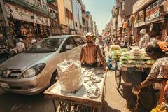 Uliczny handlowiec chodzi z fury past tłumem ludzie i pojazdy cukierki, robi ruchu drogowego dżemowi Fotografia Royalty Free