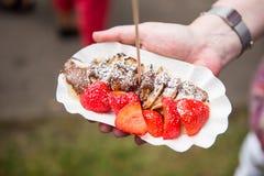 Uliczny jedzenie bliny i truskawki w ręce puchar - Obraz Royalty Free