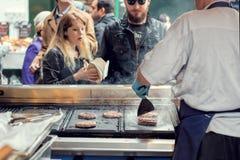 Uliczny karmowy sprzedawca piec na grillu hamburgery dla klientów zdjęcie stock