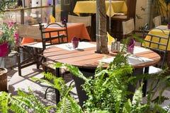 Uliczny kawiarnia taras z słuzyć drewnianymi krzesłami i stołami dekorował zielone rośliny Zdjęcia Royalty Free