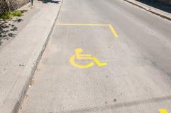 Uliczny miejsce do parkowania dla niepełnosprawni które jadą samochód z żółtym symbolem lub znakiem nieważny wózek inwalidzki obraz stock