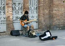 Uliczny muzyk bawić się gitarę elektryczną, śpiewa datki i zbiera, zdjęcia royalty free