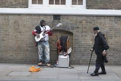 Uliczny muzyk bawić się gitarę, podczas gdy stary człowiek z trzciną chodzi za on Fotografia Royalty Free