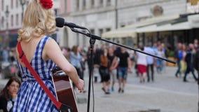 Uliczny wykonawca bawić się śpiew i gitarę w mikrofon zbiory wideo