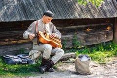 Uliczny wykonawca w ukraińskich krajowych kostiumowych sztukach wręcza lufowego organ hurdy-gurdy, koło skrzypki (,) Fotografia Stock