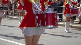 Uliczny występ świąteczny marsz dobosz dziewczyny w czerwonych kostiumach na miasto ulicie W górę żeńskich ręka doboszów zbiory wideo