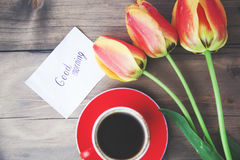 Ulips,coffee and massage. Cup of coffee, tulips and Good morning massage on wooden background Stock Photography