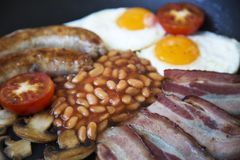 Ull English breakfast in a frying pan with fried eggs, bacon, sausages, beans and toasts. Full English breakfast in a frying pan with fried eggs, bacon Stock Image