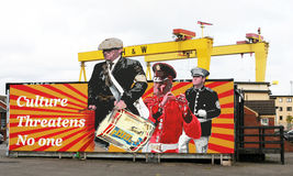 Ulster Culture Mural Belfast Northern Ireland. This mural shows Protestant Loyalist marching bands. The background show Harland and Wolff Ship Building cranes Stock Images