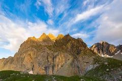 Ultima luce solare calda sulla valle alpina Fotografia Stock