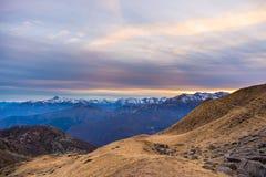 Ultima luce solare calda sulla valle alpina con i picchi di montagna d'ardore e le nuvole sceniche Alpi francesi italiane, destin Immagine Stock Libera da Diritti