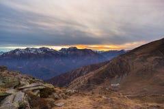 Ultima luce solare calda sulla valle alpina con i picchi di montagna d'ardore e le nuvole sceniche Alpi francesi italiane, destin Fotografia Stock