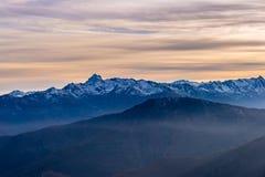 Ultima luce solare calda sulla valle alpina con i picchi di montagna d'ardore e le nuvole sceniche Alpi francesi italiane, destin Immagini Stock Libere da Diritti