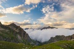 Ultima luce solare calda sulla valle alpina con i picchi di montagna d'ardore e le nuvole sceniche Alpi francesi italiane, destin Fotografia Stock Libera da Diritti